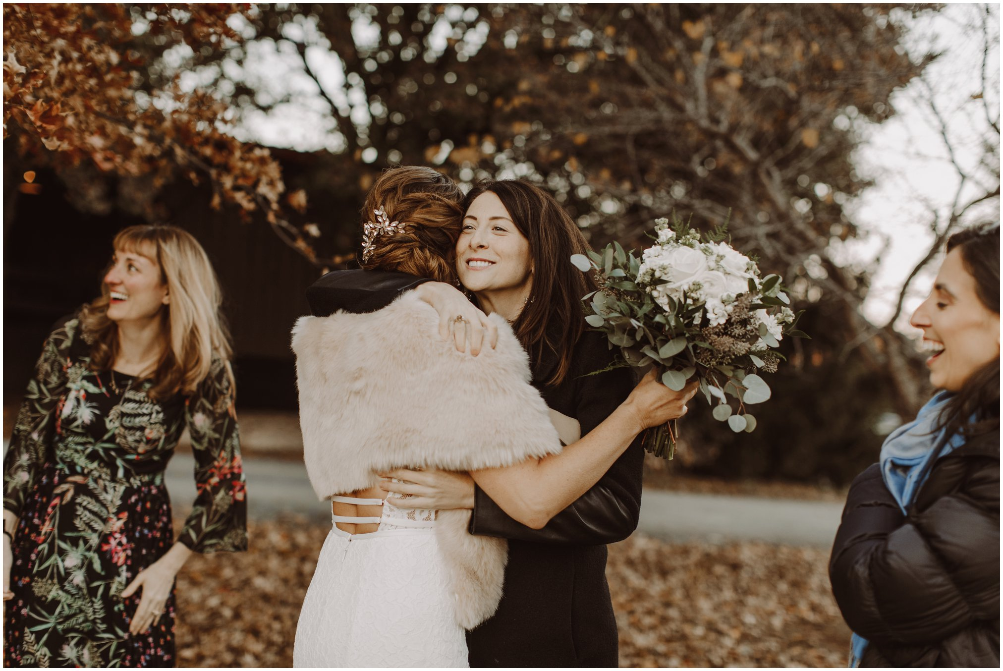 Bride and best friend hugging at wedding