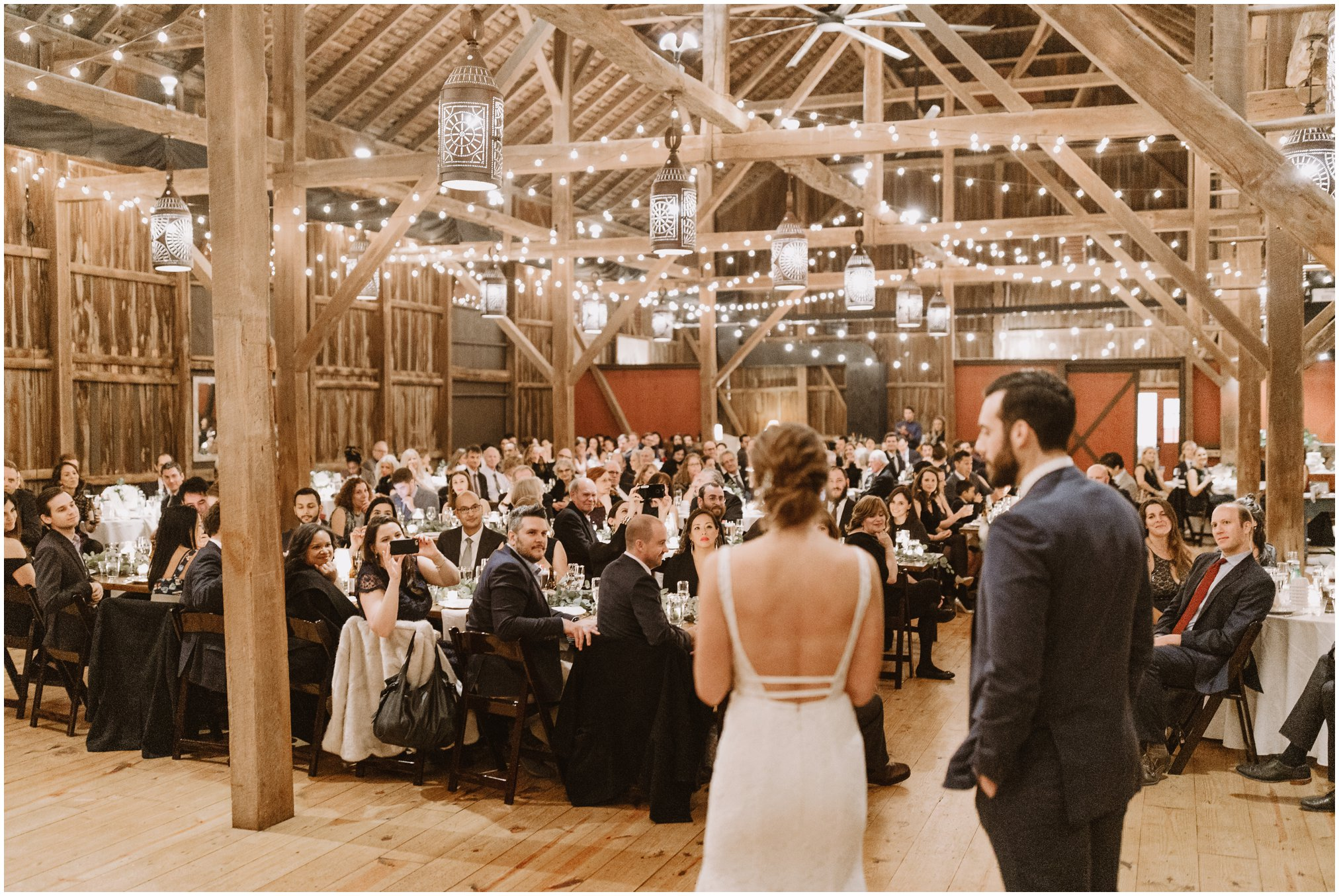 Bride and groom first dance in barn with string lights