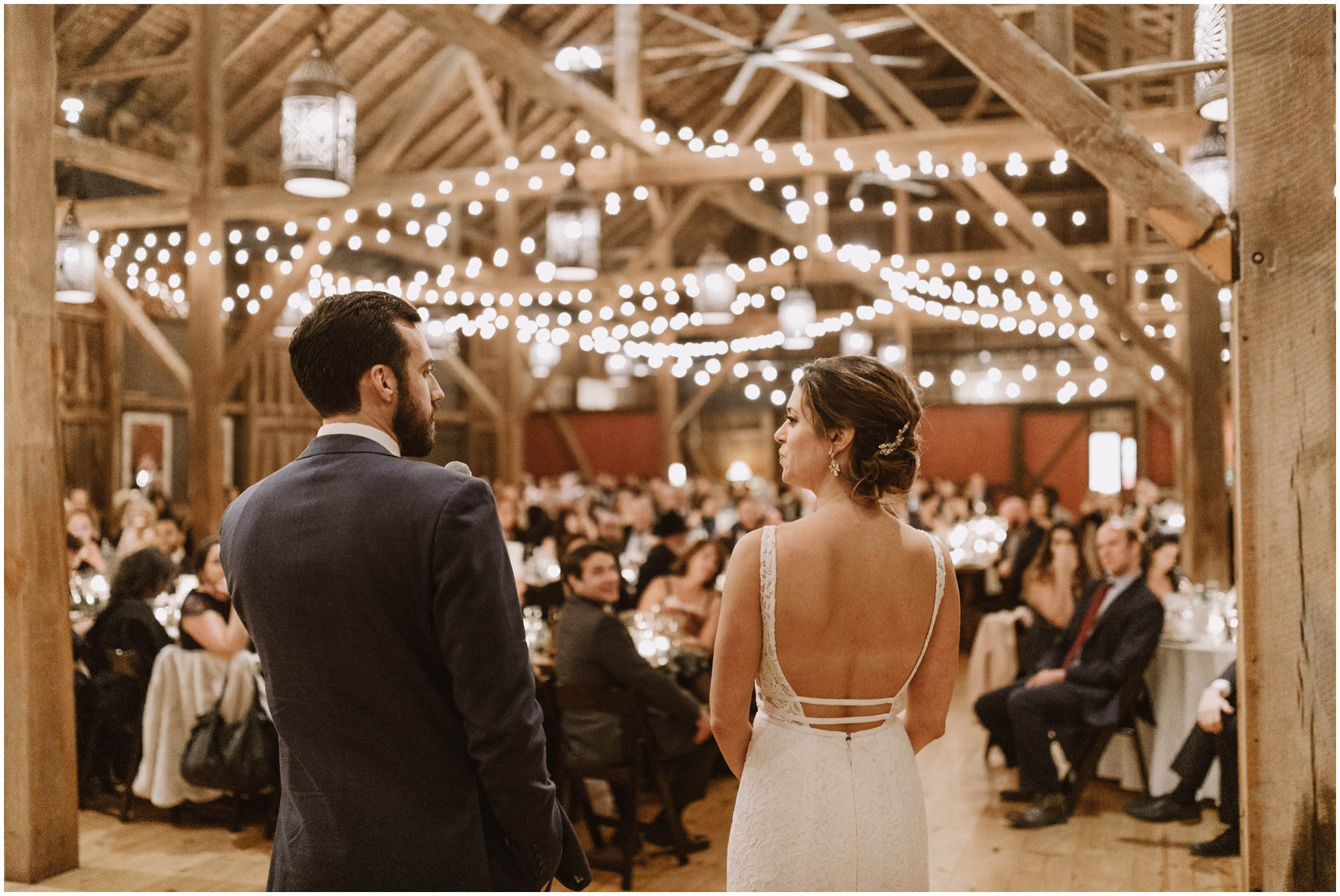 Bride and groom first dance in barn with string lights at Riverside on the Potomac