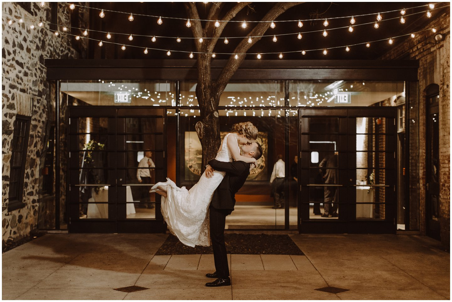 bride and groom kissing under lights