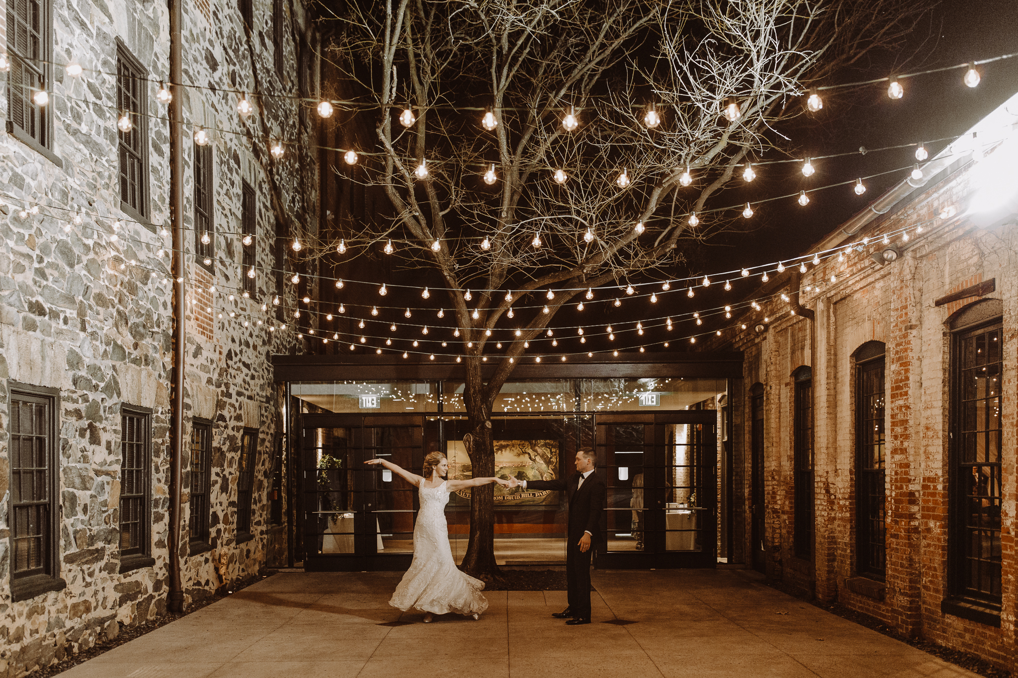 Bride and Groom Dancing Under String Lights at the Mt. Washington Mill Dye House
